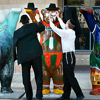 """Ultra Orthodox Jewish men put their hats on one of the """"United Buddy Bears 2007"""" near the Jerusalem City Hall on July 31, 2007.  Some 138 """"Buddy Bears"""" were created by 123 artists from 138 countries to promote tolerance and international understanding. The Buddy Bears were financed by different sponsors and will be auctioned with the proceeds going to UNICEF after a world tour. Photo By Michal Fattal/FLASH90"""