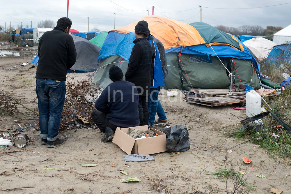 France. Refugees. Calais. So-called Jungle camp . A group of Iranians huddle around a fire.