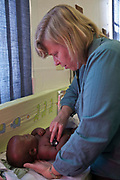 A volunteer doctor from Bigshoes Foundation examines a baby's health status as part of routine medical check-up for the adoption process in a hospital clinic Johannesburg, South Africa.  The child is currently living at the Door of Hope Children's Home and attends the clinic with a carer.