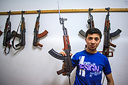 Kalashnikov assault rifles hang on the wall as Free Syrian Army (FSA) member hold his personal rifle and pose for a picture at the FSA facilities in Marea on Monday, May 28, 2012. (Photo by Vudi Xhymshiti)