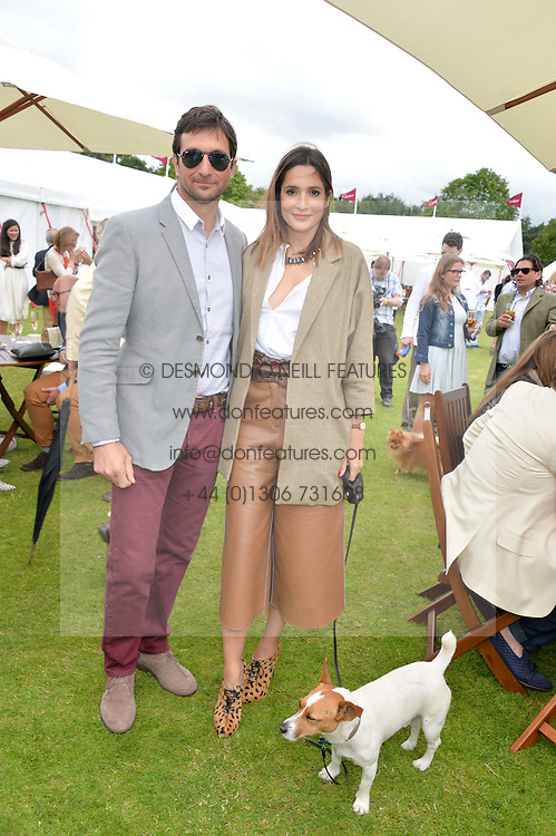 Polo player EDUARDO NOVILLO ASTRADA and ASTRID MUNOZ and her dog Egor at the Cartier Queen's Cup Final polo held at Guards Polo Club, Smith's Lawn, Windsor Great Park, Egham, Surrey on 15th June 2014.