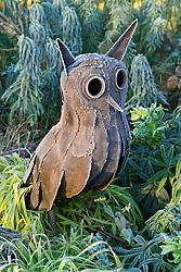 Rusty metal owl statue in frost