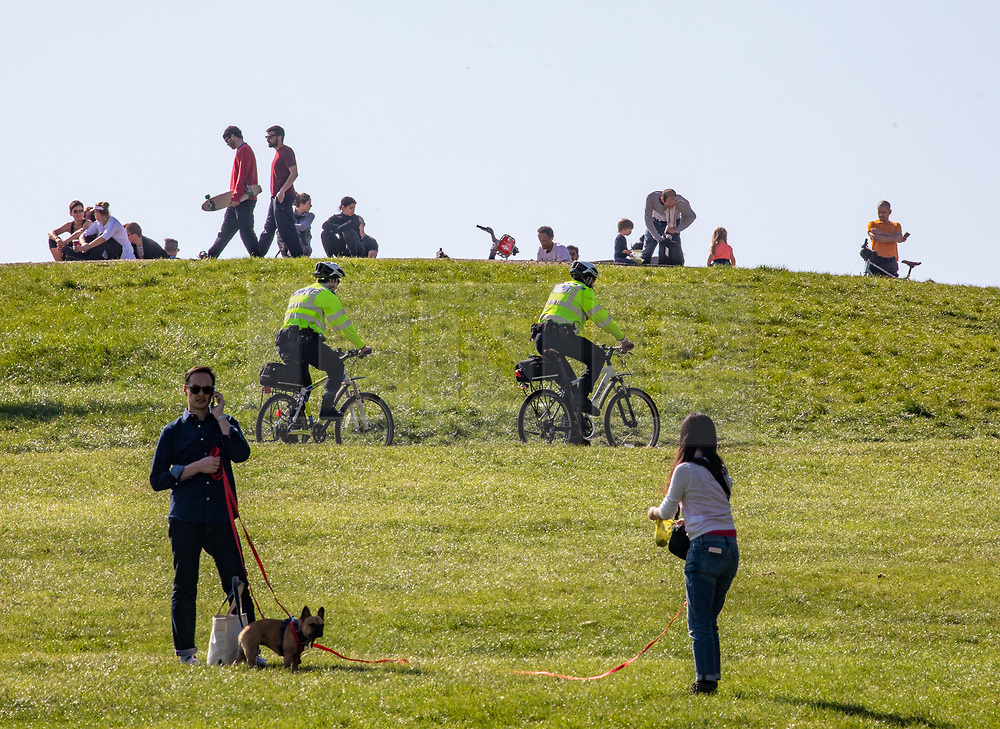 © Licensed to London News Pictures. 15/04/2020. London, UK. Members of the public enjoy the sunshine and some exercise as two Police cyclists patrol Primrose Hill in North London as Ministers decide when and how the lockdown will finish as politicians are warned that the UK could face the worst recession in 300 years. Photo credit: Alex Lentati/LNP