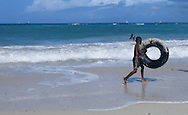 A young boy walks with an inner tube along the surf at Coco Beach in Dar es Salaam, Tanzania on Sunday, September 7, 2014.   © Chet Gordon/THE IMAGE WORKS