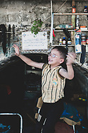 A boy dances on a chair outside his father's workshop in Aleppo, Syria. <br /> <br /> June 25, 2010
