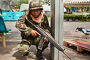 May 19 - BANGKOK, THAILAND: A Thai soldier takes shelter in a bus stop in Lumpini Park while a dead anti government protester lies in the street during the Thai government crack down against Red Shirt and anti government protesters. The Royal Thai Army attacked anti-government protesters May 19 with troops and armored personnel carriers. Photo by Jack Kurtz