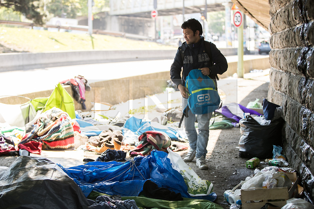 © Licensed to London News Pictures . 09/05/2017. Paris, France . A man packs shoes in to a rucksack amongst tents at the scene where French police have cleared approximately 1000 people from an ad hoc roadside camp under roadways along a central reservation , in which migrants were living , in Porte de la Chapelle in North Paris , this morning (9th May 2017) . Photo credit: Joel Goodman/LNP