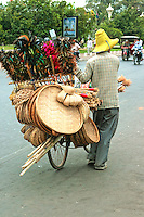 Phnom Penh Street Vendor, with brushes, baskets, wicker brooms you name it peddling his wares on the streets of the city from a bicycle.