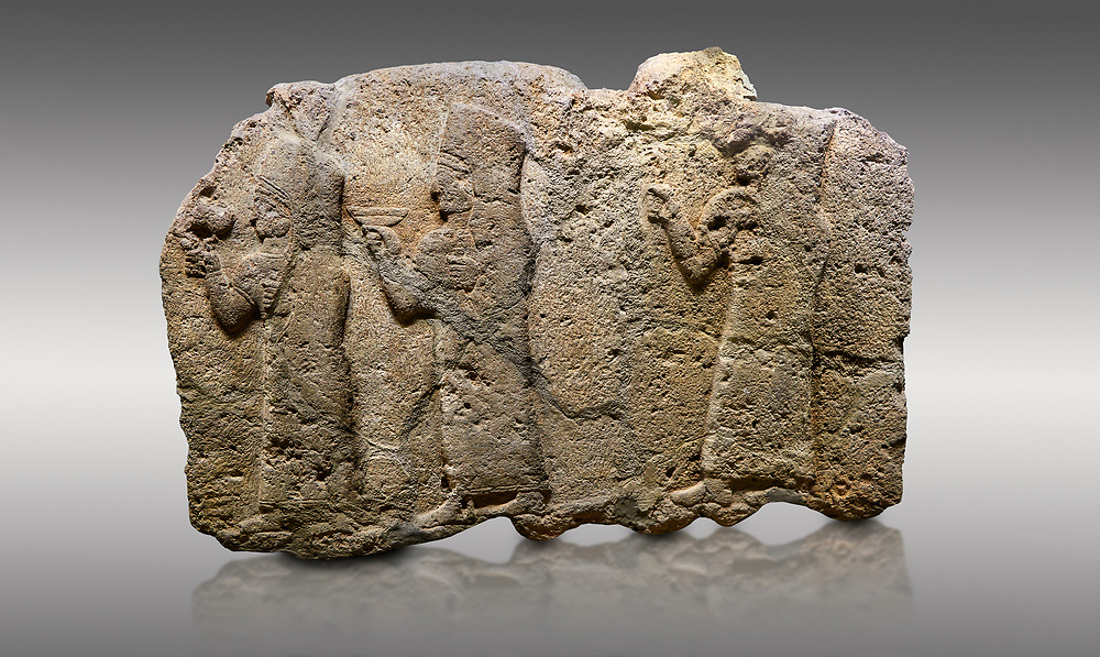 Picture & image of Hittite monumental relief sculpted orthostat stone panel of a Procession. Limestone, Karkamıs, (Kargamıs), Carchemish (Karkemish), 900 - 700 B.C. Anatolian Civilisations Museum, Ankara, Turkey.<br /> <br /> It is a depiction of three marching female figures in long dress with a high headdress (photos) at their head. These women are considered to be the nuns of the Goddess Kubaba. The figure in the front has a small animal in her right hand while the figure in the middle has a glass in his right hand. The object which the figures carry in their left is not understood.  <br /> <br /> Against a gray background. .<br />  <br /> If you prefer to buy from our ALAMY STOCK LIBRARY page at https://www.alamy.com/portfolio/paul-williams-funkystock/hittite-art-antiquities.html  - Type  Karkamıs in LOWER SEARCH WITHIN GALLERY box. Refine search by adding background colour, place, museum etc.<br /> <br /> Visit our HITTITE PHOTO COLLECTIONS for more photos to download or buy as wall art prints https://funkystock.photoshelter.com/gallery-collection/The-Hittites-Art-Artefacts-Antiquities-Historic-Sites-Pictures-Images-of/C0000NUBSMhSc3Oo