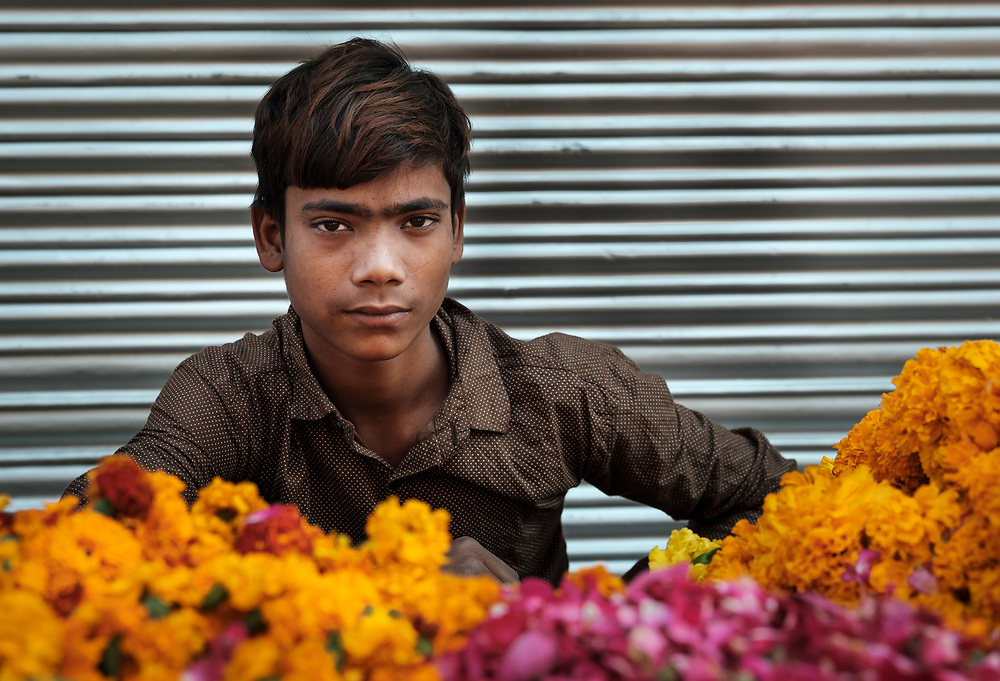 NEW DELHI, INDIA - CIRCA NOVEMBER 2018: Young boy selling marigold flowers in the  Chandni Chowk area in Old Delhi.