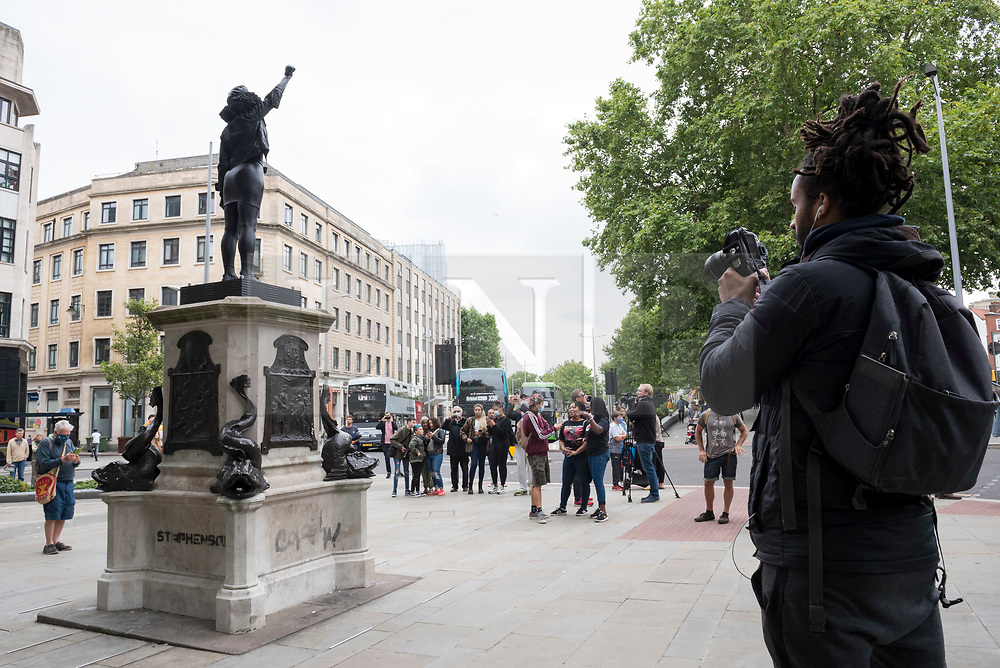 """© Licensed to London News Pictures; 15/07/2020; Bristol, UK. People view and photograph a new statue of a black lives matter protestor, Jen Reid, which has been placed on the plinth from where the statue of slave trader Edward Colston was pulled down with ropes and thrown into Bristol docks on 07 June during an All Black Lives/Black Lives Matter protest that made headlines around the world. The new sculpture is titled """"A Surge of Power (Jen Reid) 2020"""" by artist Marc Quinn and is made of black resin and steel and was put up around dawn this morning without any permission from Bristol City council. Jen Reid was at the previous protest on 07 June which was in protest for the memory of George Floyd, a black man who was killed on May 25, 2020 in Minneapolis in the US by a white police officer kneeling on his neck for nearly 9 minutes. The killing of George Floyd has seen widespread protests in the US, the UK and other countries. Photo credit: Simon Chapman/LNP."""