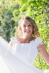 Portrait of smiling beautiful bride sitting by lakeshore, Bavaria, Germany