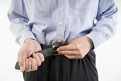 Midsection view of businessman buckling belt, Bavaria, Germany