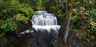 Panorama of Rolley Falls amid some fall foliage along Rolley Creek at Rolley Lake Provincial Park in Mission, British Columbia, Canada.