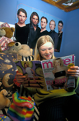 Teenage girl reading More magazine in her bedroom with Boyzone poster on wall UK