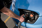 A man's hand reaches the handle of a plug after the fast charging of a Nissan Leaf electric car at an electrical charging point offering an EV 30 minute charge at a south London Nissan dealership. The Nissan Leaf (an acronym for Leading, Environmentally friendly, Affordable, Family car is a five-door hatchback electric car manufactured by Nissan and introduced in Japan and the United States in December 2010. The US Environmental Protection Agency official range is 117 kilometres (73 mi), with an energy consumption of 765 kilojoules per kilometre (34 kW·h/100 mi) and rated the Leaf's combined fuel economy at 99 miles per gallon gasoline equivalent (2.4 L/100 km). The Leaf has a range of 175 km (109 mi) on the New European Driving Cycle.