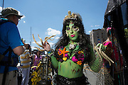 A woman in green body paint, octopus tentacles on her fingers, and with fishnets, starfish, and other sea creatures attached to her.