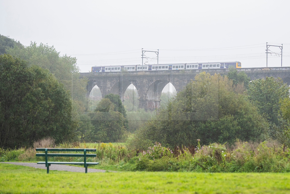 © Licensed to London News Pictures. 28/08/2020. Newton-le-Willows, UK. The 10:50 train from Earlestown towards Liverpool travels over the Sankey Viaduct on a wet morning. Photo credit: Kerry Elsworth/LNP