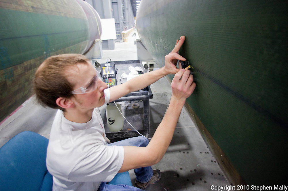 Nick Tiedje marks a spot as he checks a wind turbine blade at TPI Composites in Newton, Iowa on February 12, 2010.