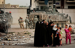 A group of women in the Baghdad Shiite neighborhood of Shula wait to be searched by a female soldier attached to 4-14 Cavalry - a unit within the 172nd Stryker Brigade. The scene took place during an operation by bolstered US and Iraqi forces in the hopes of getting a handle on the extraordinary numbers of sectarian killings in Baghdad - was carried out in Baghdad, Iraq on Sunday August 20, 2006. The brigade, which was in the process of rotating home at the end of a year tour in Mosul and northwestern Iraq, was diverted to the capital for an undetermined number of additional months.