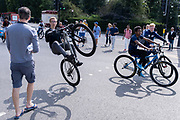 Male youths perform wheelies as they cycle past pedestrians waiting to cross the road at Marble Arch, on 11th August 2021, in London, England.