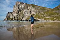 Female hiker walks in sea below Ryten at Kvalvika beach, Moskenesøy, Lofoten Islands, Norway