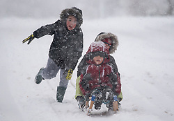 © Licensed to London News Pictures. 10/12/2017. Tring, UK. Children play on a sledge in heavy snow fall in the town of Tring in Buckinghamshire, England as parts of the south east of England are blanketed with snow for the first time this winter. Photo credit: Ben Cawthra/LNP
