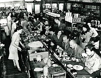 1945 Sidney Skolsky and Herman Hover (owner of Ciro's) )at the counter in the center) eat at Schwab's Pharmacy