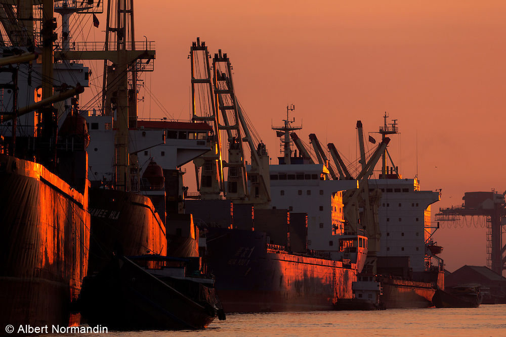 Long line of freighter ships in port, Yangon River