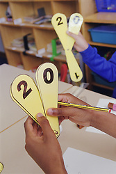 Close up of primary school children counting using number fans in practical maths lesson,