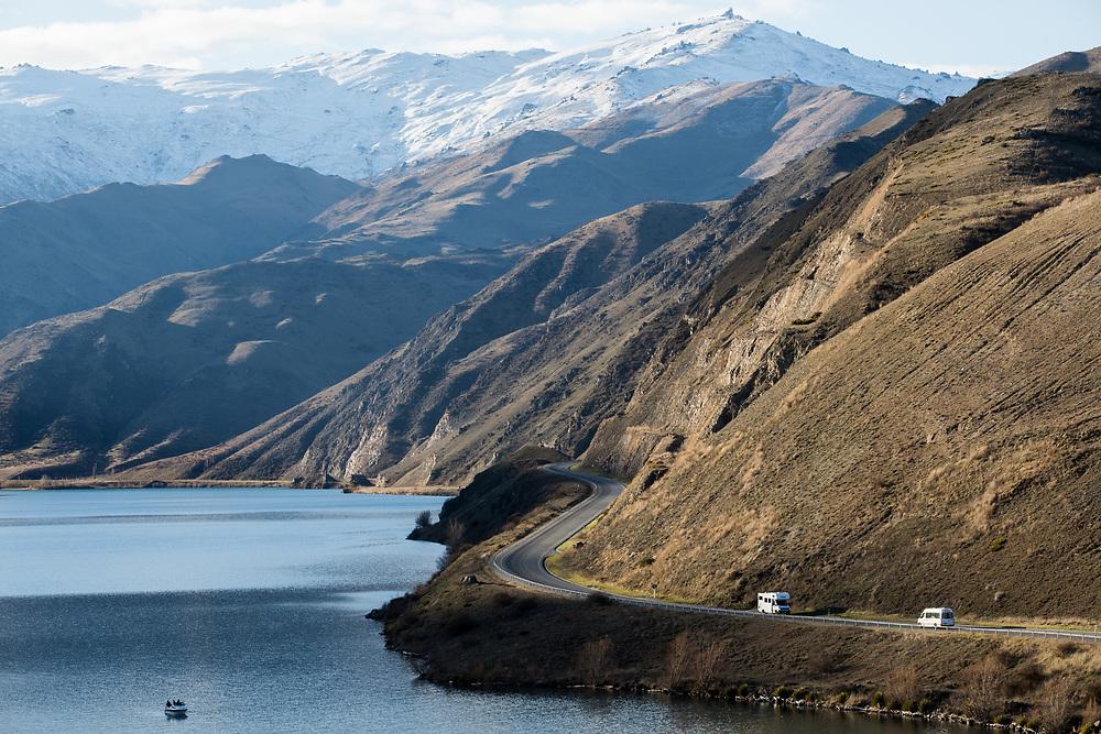 Campervans travelling alongside Lake Dunstan, Clyde, Central Otago.