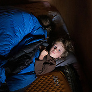 A child is awake in his sleeping bag while his mother sleeps.