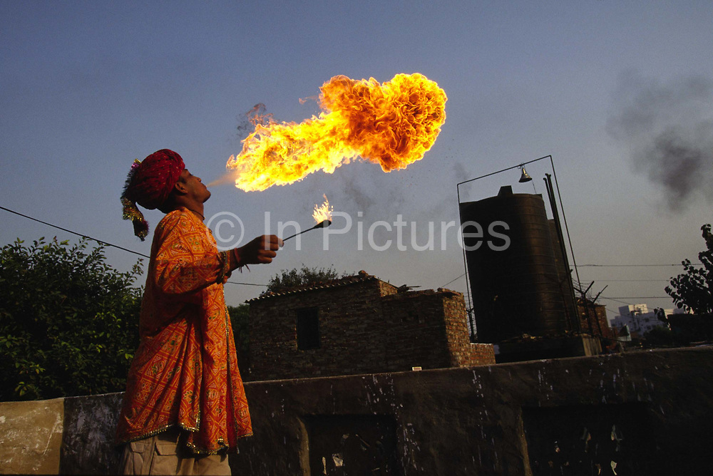 Vishal Bhatt breathes fire above Shadipur. The Bhatts, a huge extended family of puppeteers, singers and dancers are all from Rajasthan. When the traditional nomadic lifestyles of courtly entertainers declined, the families moved to the cities to find work.<br /> The Kathiputli Colony in the Shadipur Depot slum is home to hundreds of (originally Rajasthani) performers. The artistes who live here - from magicians, acrobats, musicians, dancers and puppeteers are often international renowed by always return to the Shadipur slum.