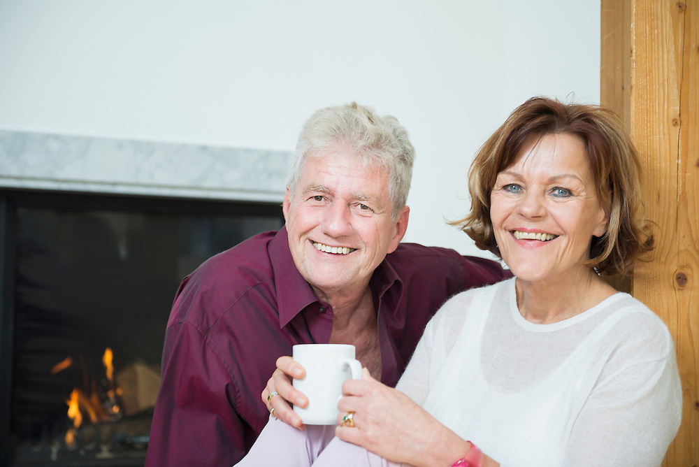 Portrait of senior couple sitting in front of fireplace, smiling