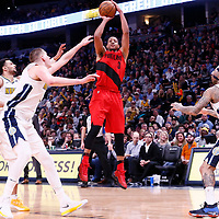 09 April 2018: Portland Trail Blazers guard CJ McCollum (3) takes a jump shot over Denver Nuggets guard Jamal Murray (27) and Denver Nuggets center Nikola Jokic (15) during the Denver Nuggets 88-82 victory over the Portland Trail Blazers, at the Pepsi Center, Denver, Colorado, USA.