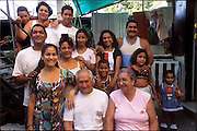(MODEL RELEASED IMAGE). Surrounded by the in-laws and cousins with whom they share a Colonial-era house, the Costa family: Ramon Costa Allouis, Sandra Raymond Mundi, and their children Lisandra, and Fabio, in the courtyard of their extended family's home in Havana, Cuba. (Supporting image from the project Hungry Planet: What the World Eats.)