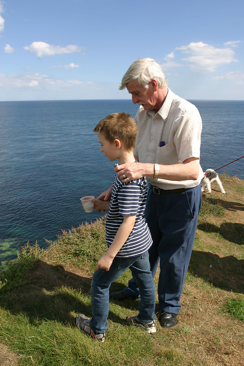 Young boy scattering grandfather's ashes, Bridlington, UK