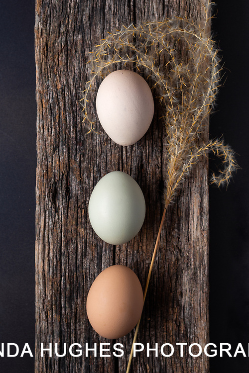 Still life of three eggs on a wooden plank with a grass stem
