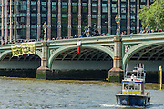 A police boat patrols under the banner. A protest organised by UK Uncut marches from Waterloo Station towards Parliamentwhere a large banner is painted on Westminster Bridge. It is then lowered over the side of the bridge wighted down by milk cartons. Eneventually the Police force its removal to the embankment in front of St Thomas' Hospital. The banner read - 312bn more cuts, £120hn tax dodged, AUSTERITY IS A LIE - which sums up what they were protesting about.