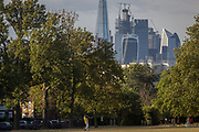 A cricket player throws the ball back during a game in front of the skyline of the City of London's financial district, in Ruskin Park, on 8th August 2018, in London, England.