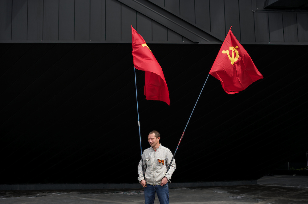 A Ukrainian man, holding flags of the communist party, attend a ceremony that marks 69 years since the Soviets defeated the Nazis, at the War Memorial in central Donetsk, amid tensions over the referendum for autonomy of the region to be held over the weekend.