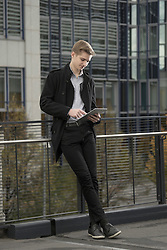 Teenage businessman waiting for someone and using digital tablet against railing, Bavaria, Germany