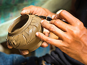 29 AUGUST 2105 - KO KRET, NONTHABURI, THAILAND: A man etches a pot in a pottery factory on Ko Kret. Ko Kret is a small island in the Chao Phraya River in Nonthaburi province north of Bangkok. It is some 2 km long and 1 km wide. It has seven main villages, the largest and most populous being Ban Mon. Ko Kret was created in 1722 when a canal was dug in the Chao Phraya River to bypass a bend. Most of the people on the island are ethnically Mon, from the hills of western Thailand and eastern Myanmar (Burma). The island is popular as a weekend daytrip from Bangkok. The island is famous for the Mon style pottery made on the island.   PHOTO BY JACK KURTZ