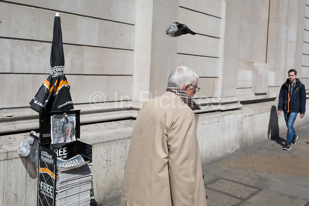 City workers walk past Evening Standards with Prime Minister Theresa May on the front page, asking the nation to trust her and yesterdays snap election announcement, outside the Bank of England in the heart of the capitals financial district, on 19th April, in the City of London, England.