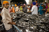 A men distribute empty metal plates to the people queuing for their thali, the indian meal.