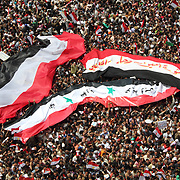 Two enormous Egyptian flags and one Iraqi flag converge over the heads of protesters in Cairo's Tahrir Square during the Day of Justice and Cleansing.