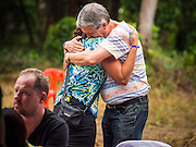 26 DECEMBER 2014 - MAE KHAO, PHUKET, THAILAND:  PAUL BILNEY, originally from Australia and now living in Phuket, comforts HELEN KEOGH, also Australian, at the Tsunami Memorial Wall in Mae Khao, Phuket. Bilney and Keogh helped with recovery efforts after the tsunami. The wall is located at the site that was used as the main morgue for people killed in the tsunami and hosts an annual memorial service. Nearly 5400 people died on Thailand's Andaman during the 2004 Indian Ocean Tsunami that was spawned by an undersea earthquake off the Indonesian coast on Dec 26, 2004. In Thailand, many of the dead were tourists from Europe. More than 250,000 people were killed throughout the region, from Thailand to Kenya. There are memorial services across the Thai Andaman coast this weekend.   PHOTO BY JACK KURTZ