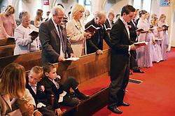 Wedding guests standing in church pews singing hymn,