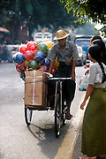 Cycle rickshaw loaded with London Cigarettes and coloured balls. Rangoon, Burma 2001