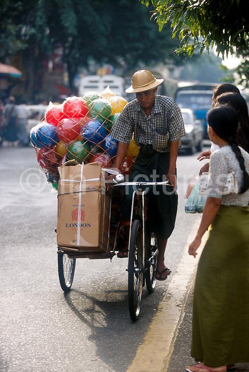 Cycle rickshaw loaded with London Cigarettes and coloured balls. Rangoon, Burma 2001